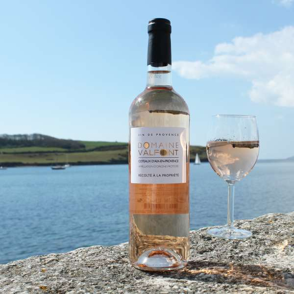 Domaine Valfont Provence rose with glass on st mawes harbour wall with sea in background