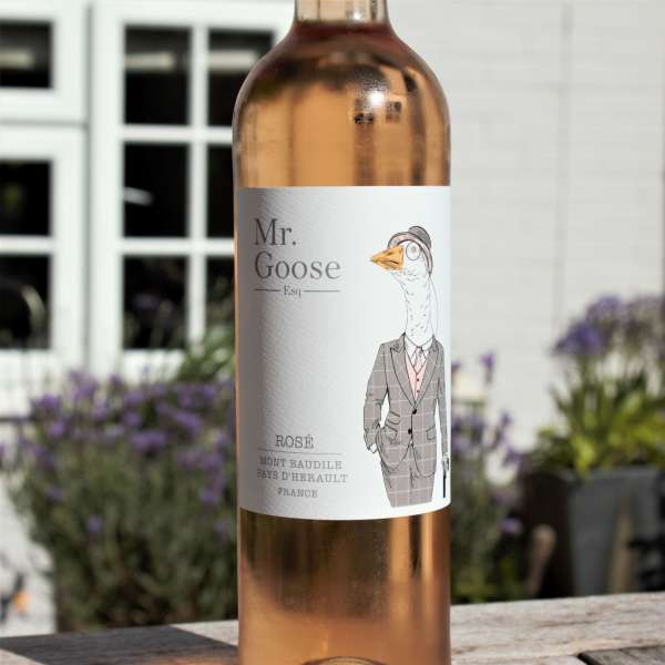 Mr Goose French rose wine on garden table with lavender plants behind